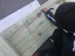 student signing the bench with the names of the students who built it